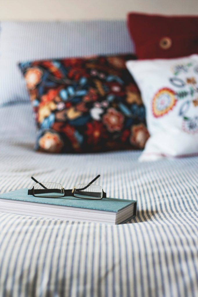 book sitting on a bed with reading glasses - use a book to set secure passwords