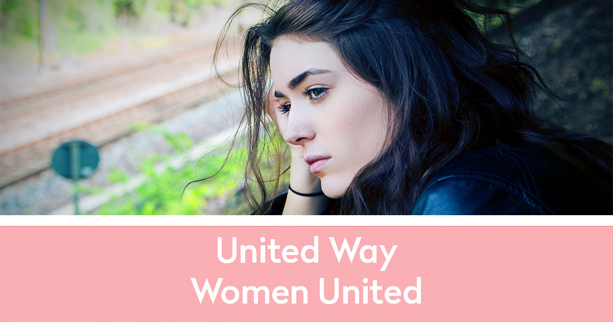 Beautiful woman with dark hair sitting on a hill near the railroad looking to the left with a sad expression | United Way | Women United