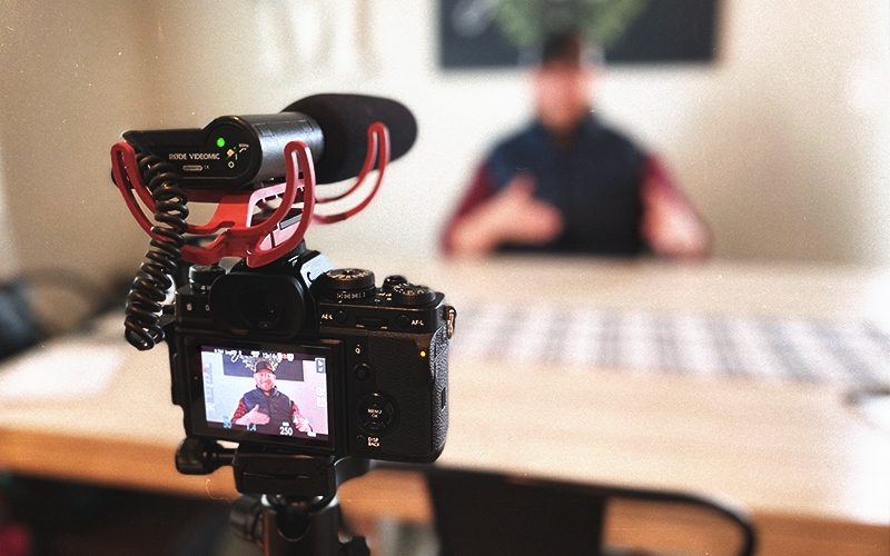 Image of a person filming a video interview shot from behind the lens