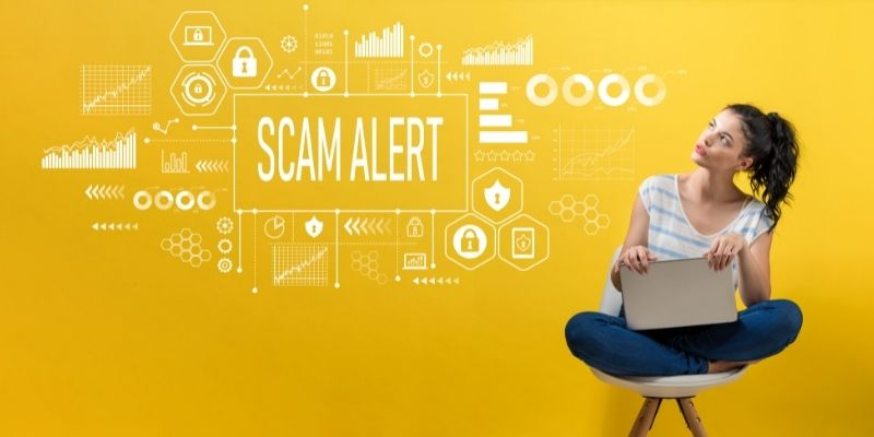 """Yellow background with white charts and figures with the words """"SCAM ALERT"""" and a woman sitting on a stool with her laptop"""