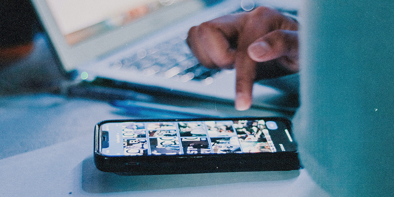 Close up of hand scrolling through mobile phone