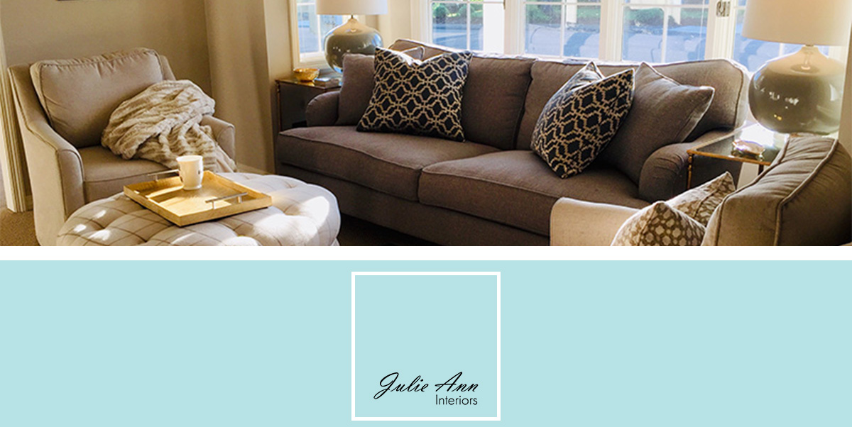 Julie Ann Interiors logo white square with black text on a robins egg blue background with a living room above it